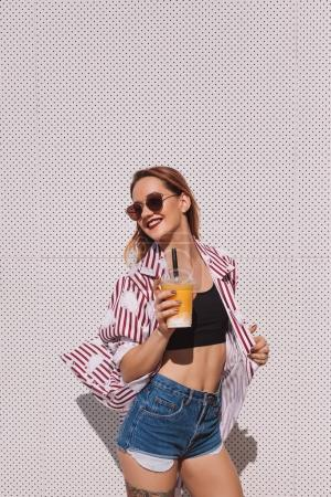 stylish young woman with mango shake in plastic cup