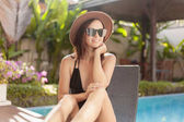 attractive young woman in swimsuit and hat sitting in sun lounge at poolside