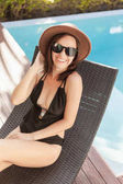 happy young woman in swimsuit and hat sitting in sun lounge at poolside