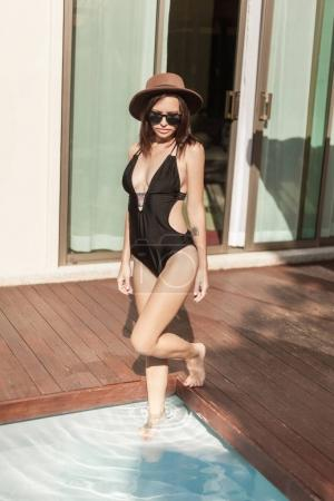 stylish young woman in swimsuit and hat going into swimming pool