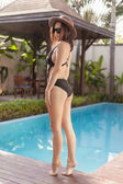 beautiful young woman in one-piece swimsuit and hat at poolside of hotel