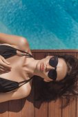 top view of beautiful young woman in black swimsuit lying at poolside