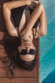 top view of attractive young woman in black swimsuit lying at poolside