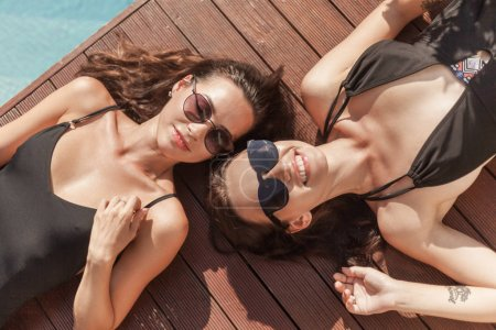 Photo for Top view of happy young women in swimsuits lying on poolside - Royalty Free Image