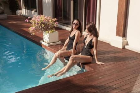 beautiful young women in swimsuits sitting at poolside with legs in water