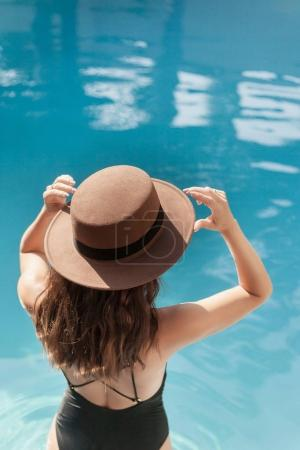 beautiful young woman in swimsuit and stylish hat at pool