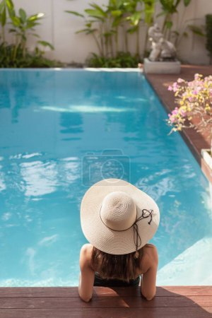 back view of young woman in swimsuit and hat sitting in pool of hotel