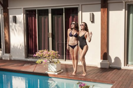 attractive young women in bikini and swimsuit standing at poolside in front of house