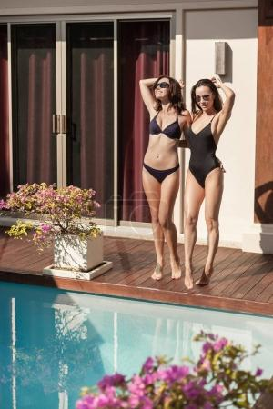 attractive young women in bikini and swimsuit posing at poolside of hotel