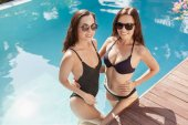 attractive young women in bikini and swimsuit standing in pool