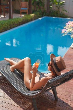 young woman in bikini lying in sun lounge at poolside