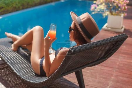 Photo for Stylish young woman in bikini lying in sun lounge at poolside - Royalty Free Image