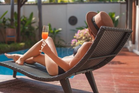 relaxed young woman in bikini lying in sun lounge at poolside