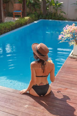 Photo for Back view of attractive young woman in bikini sitting at poolside - Royalty Free Image