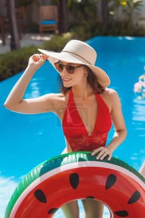 stylish young woman in swimsuit with inflatable ring at poolside