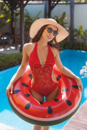 attractive young woman in swimsuit with watermelon inflatable ring at poolside