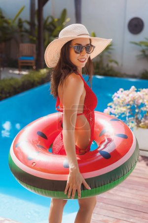 beautiful young woman in swimsuit with inflatable ring at poolside