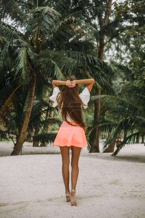 back view of young girl posing on sandy beach with palms