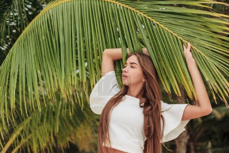 attractive girl posing with palm leaf on beach