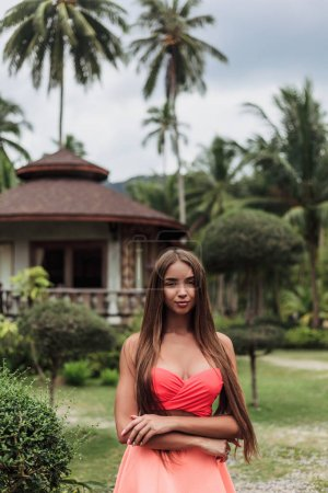attractive girl on tropical resort with bungalow and palms