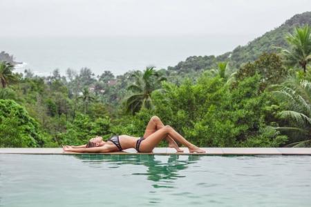 Photo pour Belle fille en bikini relaxant à la piscine sur station tropicale - image libre de droit