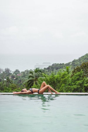 girl resting at swimming pool on tropical resort