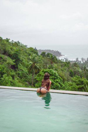 back view of girl posing in swimming pool on tropical resort