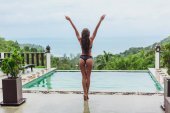 back view of girl posing at swimming pool on tropical resort