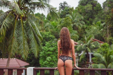 Photo for Rear view of young girl in bikini on balcony looking at tropical forest - Royalty Free Image