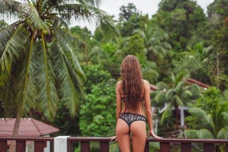 Photo pour Vue arrière de la jeune fille en bikini sur balcon donnant sur la forêt tropicale - image libre de droit