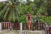 rear view of young girl on balcony looking at tropical rainforest