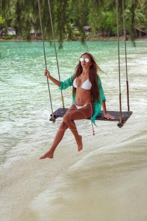 beautiful girl on swing at tropical sea beach