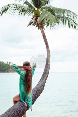 back view of girl with long hair sitting on palm tree over the ocean