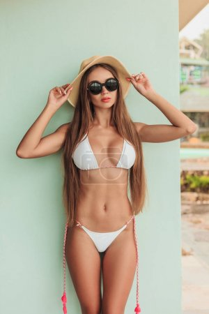 attractive slim girl posing in stylish bikini, sunglasses and hat