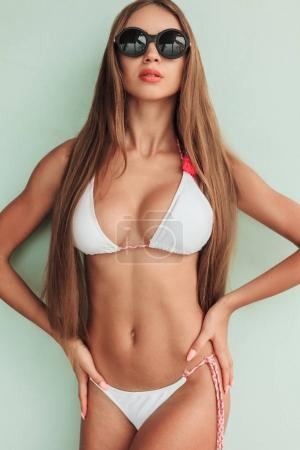 girl posing in stylish bikini and sunglasses