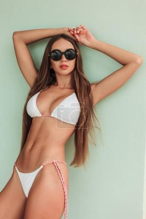 Photo for Beautiful girl with long hair posing in stylish bikini and sunglasses - Royalty Free Image