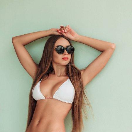 attractive girl with long hair posing in stylish bikini and sunglasses