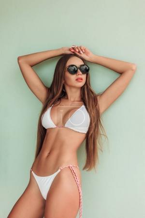 caucasian girl with long hair posing in stylish bikini and sunglasses