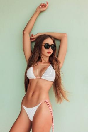 girl with long hair posing in stylish bikini and sunglasses