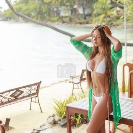 beautiful girl posing in white bikini on tropical resort