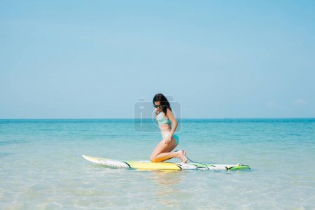 Photo for Beautiful girl in bikini with paddle board on tropical beach - Royalty Free Image