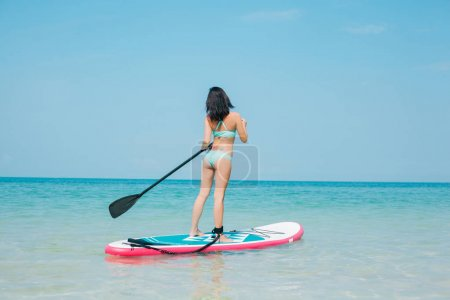 Photo for Back view of girl on stand up paddle board on sea at tropical resort - Royalty Free Image