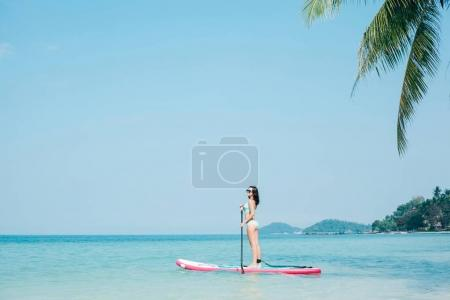 Photo for Young girl on stand up paddle board on sea at tropical resort - Royalty Free Image