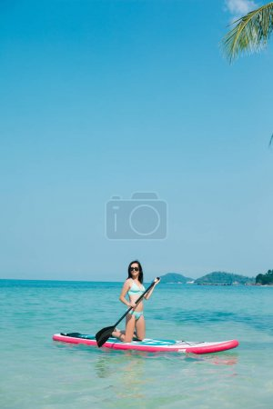 young girl on stand up paddle board on sea at resort