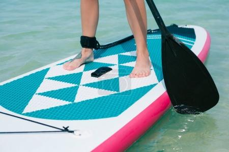 low section view of woman on stand up paddle board on sea at tropical resort