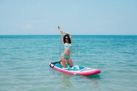 Photo pour Belle femme posant sur paddle board sur mer - image libre de droit