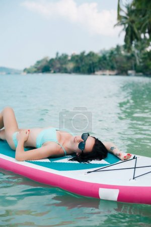 Photo for Beautiful girl lying on paddle board on sea at tropical resort - Royalty Free Image