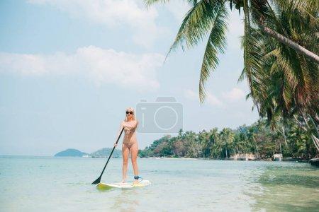 Photo pour Femme blonde debout sur le paddleboard sur la mer à la station tropicale - image libre de droit