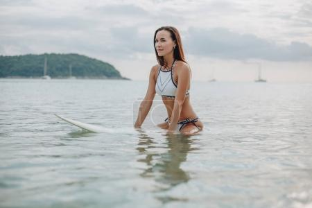 Photo for Attractive young woman in bikini sitting on surfboard in water - Royalty Free Image