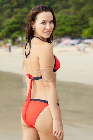 smiling young woman in red bikini on resort